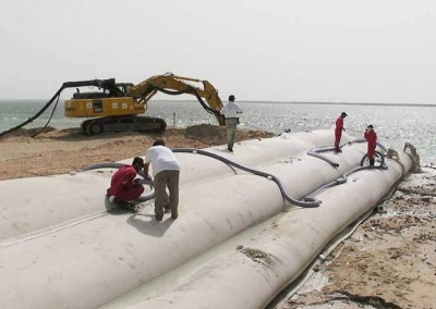 Excavator memasang pompa pengeruk pengikat yang memindahkan pasir jarak jauh ke dalam tabung geo